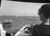 Roger Vadim driving a speed boat while going towards and being watched by Jane Fonda.