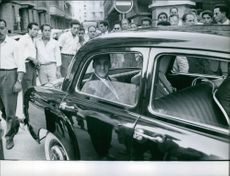 Ferhat Abbas sitting inside the car, people looking at him, 1959.