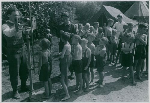 The bunker children line up to have their weight measured on a weighing scale.