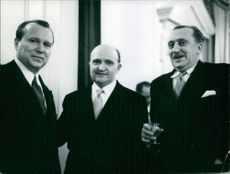 Three men in a suit smiling and looking at camera.