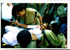 Policewomen drag an activist of the Communist Party of India.