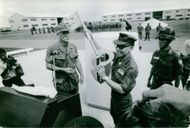 Military officer presenting a key to the press, smiling, with soldiers in formation at the back, in Vietnam, 1972.