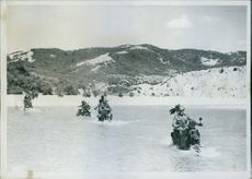 Soldiers riding on motor cycle in sea.