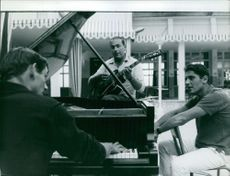 Sacha Distel sings while other two men plays the guitar and a piano.