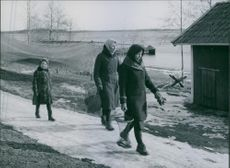 Women walking in the village, holding net containing fish.1944.