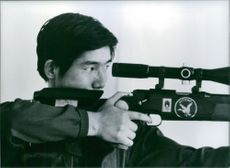 Yu Jiping aiming his rifle gun. 1980.