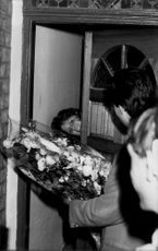 Sarah Ferguson looks out through the door when the party arrives with a large bouquet of flowers.