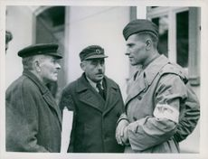 First Lieutenant Thoo Prisajunic (right), Russian liaison officer with the Ninth U.S. Army, explains to the burgomeister of Nieder Lepte (left) that Russian columns are approaching from Berlin.