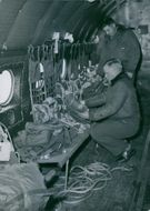 Two soldiers looking at the parachute aboard the plane. 1950.
