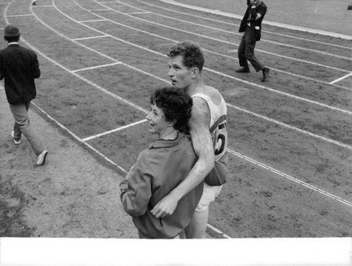 An athlete walking with a lady on the track field, 1964.