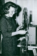 Princess Beatrix standing, looking at an object and smiling.