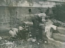 A man getting water from a faucet in the bathroom destroyed due to bombing. 1915