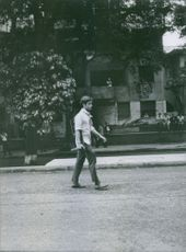 A man walking on the street while holding a gun in public.