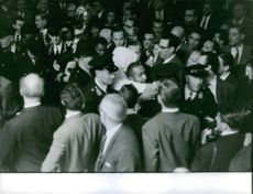Cops assisting Sugar Ray Robinson to come out from the crowd, 1962.