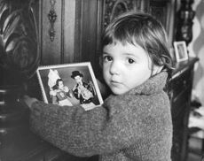 A little kid holding a photograph, looking into the camera.