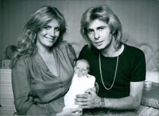 Julie Forsyth and Dominic Grant posing with their new born baby and smiling.