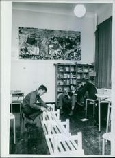Two men reading a book, while the other man is hammering a nail into wood.