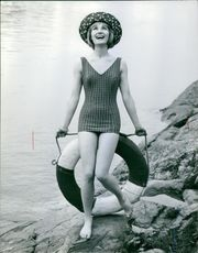 Woman standing on the rock, beside the coast holding a round inflated tube.1962
