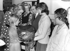 Prince Laurent together with his mother, Queen Paola receiving a gift from a woman.