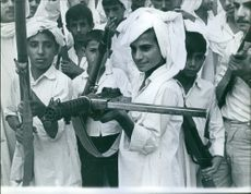 Children holding guns in their hands and posing.