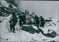 A photo of British soldiers carrying a wounded comrade to forbandsplatsen during the raid on Vågsøy . January 1942