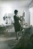 Marie-Helene Arnaud standing in a room while painting, 1962.