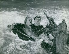 Brigitte Bardot trying to escape in water with man.  From a moviescene