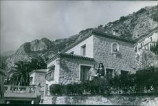 """Man and woman standing on the roof of their royal house on the mountains.  """"Peter of Yugoslavia ___""""  1960"""