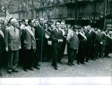 Pierre Mendès France standing with people in the street of Paris.
