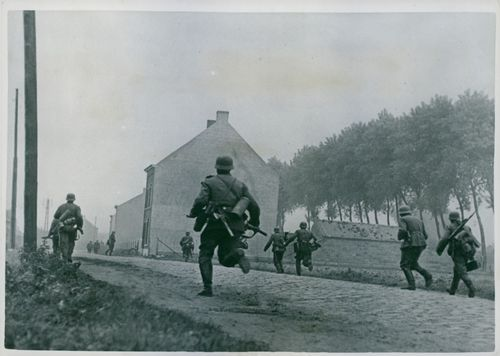 Soldiers running on the road as they engage in battle.