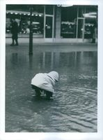 A child playing on a street flooded with water.