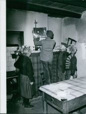 A photo of a man holding and hanging portrait on the wall in the house with him are old man and two old woman watching him fixing.