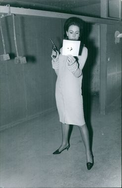 Ann Sidney, Miss World, looking at paper and holding gun.