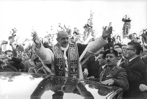 Pope Paul VI standing with hands wide open.