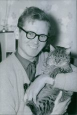 A photo of Gordon Dykes holding a cat while smiling.