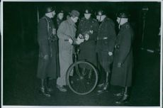 German occupation Five military men surrounds a man with a bicycle as he shows a paper to them, 1943.