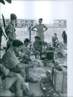 Soldiers gathered in the street while siting and relaxing in Lebanon.