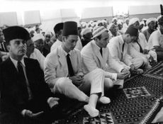 Aga Khan IV praying with other people.