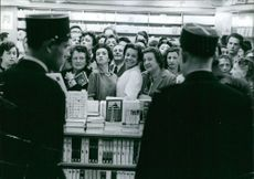 People gathered in a book shop, some are smiling. 1959.