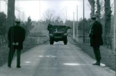 Soldiers standing and looking the army vehicle coming. 1969
