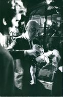 Otto Preminger pouring water on the doll, on the set of