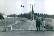 Man and woman moving towards the sculptor of the creature on the pole.