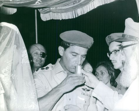 Yael Dayan is about to drink the wine during his wedding while behind him is his father Moshe Dayan looking happily.