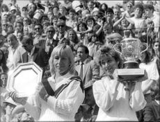 Martina Navratilova and Chris Evert proudly hold their trophies after the final at Stade Roland Garros