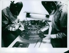 Two men looking at the machine part while working.