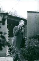 Man walking, covering his face with a paper.