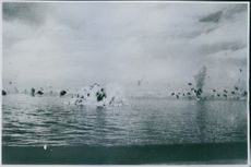Japanese bomber plane plunge into the sea. Smoke puffs from anti-aircraft shells are seen to the right and left.