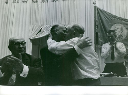 Two men embracing each other, people clapping. 1964