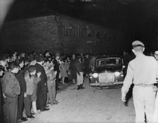 A prominent person arriving in a place in Israel with crowd standing on the side of the street welcoming him, 1963.