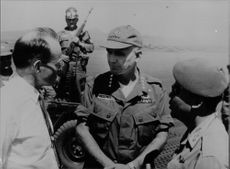 Army officers talking to a man in Vietnam.